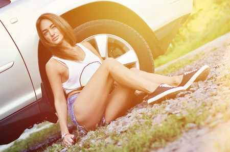 Young and attractive sexy caucasian girl in denim shorts with big and old spanner close to a silver off-road car with an open hood. The concept of repair and maintenance of a car Imagens