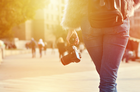 Rear view of a female photographer with a modern SLR camera in her hand against a blurred crowded street