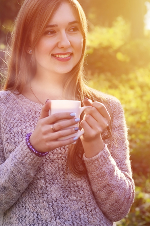 Portrait of a cheerful young smiling woman in autumn forest holding ceramic white coffee cup in autumn forest outdoors