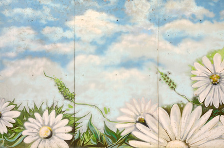 Background texture of wall with graffiti paintings. Blue cloudy sky and white flowers