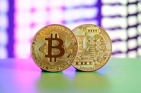 Two gold bitcoins lie on the green surface on the background of the display, which shows the process of mining the crypto currency