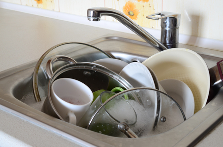 Dirty dishes and unwashed kitchen appliances filled the kitchen sink 免版税图像 - 100156094