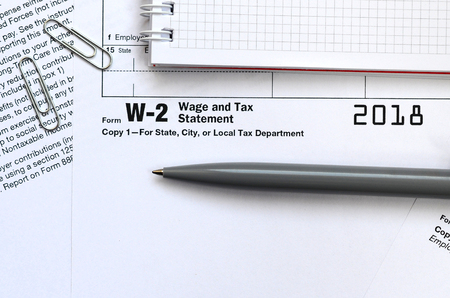 The pen and notebook on the tax form W-2 Wage and Tax Statement. The time to pay taxes Banco de Imagens