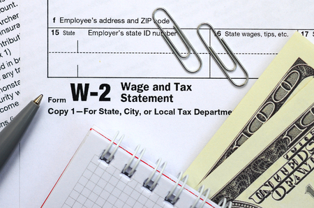 The pen, notebook and dollar bills is lies on the tax form W-2 Wage and Tax Statement. The time to pay taxes Banco de Imagens