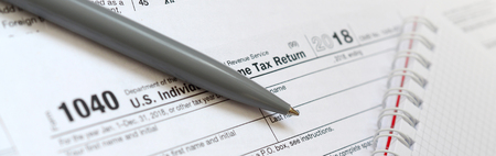 The pen and notebook is lies on the tax form 1040 U.S. Individual Income Tax Return. The time to pay taxes