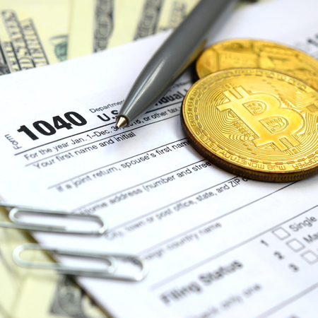 The pen, bitcoins and dollar bills is lies on the tax form 1040 U.S. Individual Income Tax Return. The time to pay taxes Stockfoto