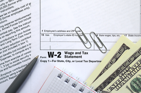 The pen, notebook and dollar bills is lies on the tax form W-2 Wage and Tax Statement. The time to pay taxes Stock Photo