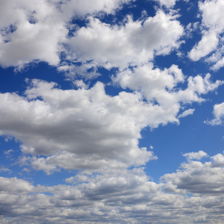 A blue sky with lots of white clouds of different sizes