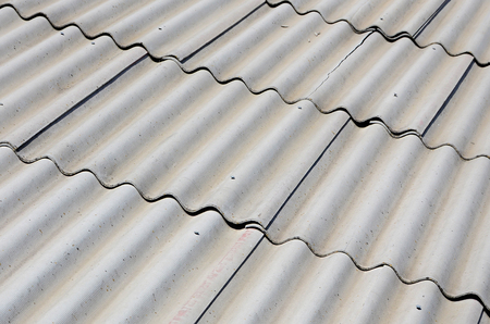 A fragment of a gray slate roof of an old sample made of asbestos material Stock Photo