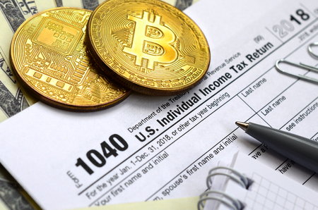 The pen, bitcoins and dollar bills is lies on the tax form 1040 U.S. Individual Income Tax Return. The time to pay taxes Фото со стока