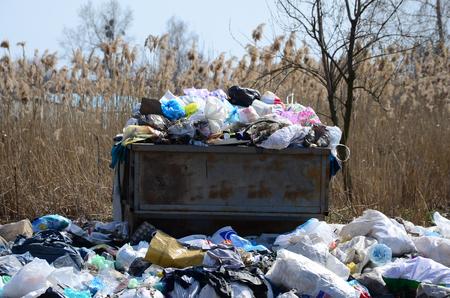 El bote de basura está lleno de basura y desperdicios. Retirada inoportuna de basura en zonas pobladas Foto de archivo