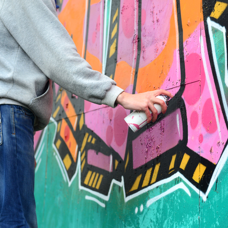 Hand of a young guy in a gray hoodie paints graffiti in pink and green colors on a wall in rainy weather