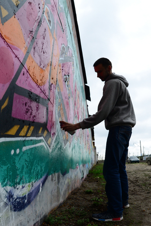 A young guy in a gray hoodie paints graffiti in pink and green colors on a wall in rainy weather. Fisheye shot