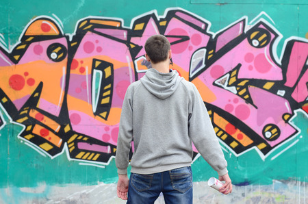 A young graffiti artist in a gray hoodie looks at the wall with his graffiti in pink and green colors on a wall in rainy weather. Street art concept Stock Photo
