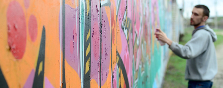 A young guy in a gray hoodie paints graffiti in pink and green colors on a wall in rainy weatherю Focus on the fragment of wall and blurred artist
