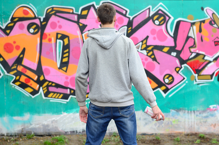 A young graffiti artist in a gray hoodie looks at the wall with his graffiti in pink and green colors on a wall in rainy weather. Street art concept Stock fotó