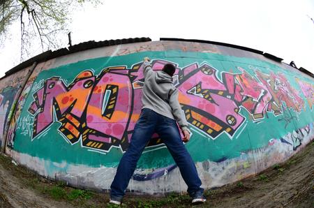 Un joven con una sudadera con capucha gris pinta graffiti en colores rosa y verde en una pared cuando llueve. Disparo de ojo de pez