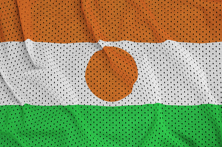 Niger flag printed on a polyester nylon sportswear mesh fabric with some folds 免版税图像
