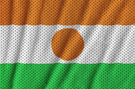 Niger flag printed on a polyester nylon sportswear mesh fabric with some folds Stock Photo