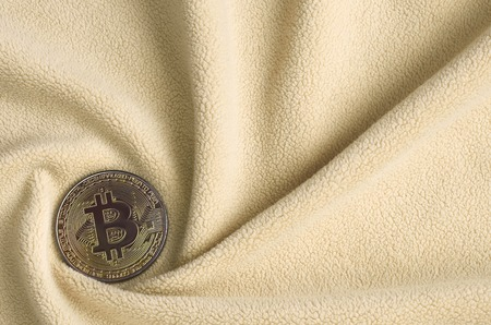 The golden bitcoin lies on a blanket made of soft and fluffy light orange fleece fabric with a large number of relief folds. The shape of the folds resembles a fan from a video card cooler