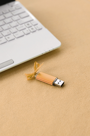Orange usb flash memory card with a bow lies on a blanket of soft and furry light orange fleece fabric beside to a white laptop. Classic female gift design for a memory card