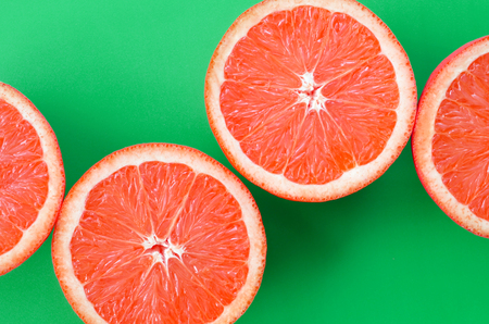 Top view of a several grapefruit slices on bright background in green color. A saturated citrus texture image