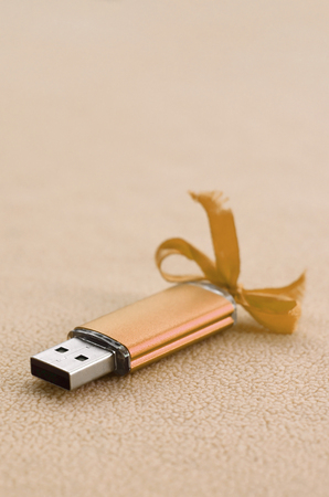Orange usb flash memory card with a blue bow lies on a blanket of soft and furry light orange fleece fabric. Classic female gift design for a memory card