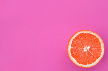 Top view of an one grapefruit slice on bright background in purple color. A saturated citrus texture image