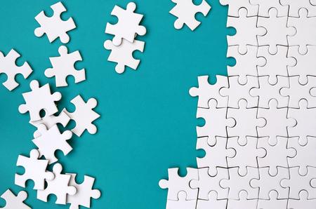 Fragment eines gefalteten weißen Puzzles und eines Stapels ungekämmter Puzzle-Elemente vor dem Hintergrund einer blauen Oberfläche. Texturfoto mit Platz für Text Standard-Bild