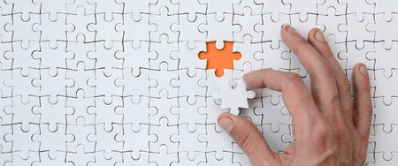 The texture of a white jigsaw puzzle in the assembled state with one missing element that the male hand puts in Reklamní fotografie