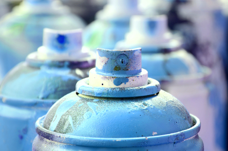 A lot of dirty and used aerosol cans of bright blue paint. Macro photograph with shallow depth of field. Selective focus on the spray nozzle Stock Photo