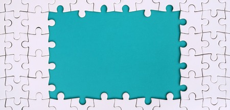 Framing in the form of a rectangle, made of a white jigsaw puzzle around the blue space