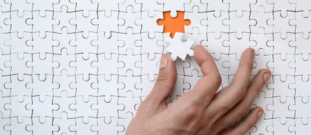 The texture of a white jigsaw puzzle in the assembled state with one missing element that the male hand puts in Stock Photo