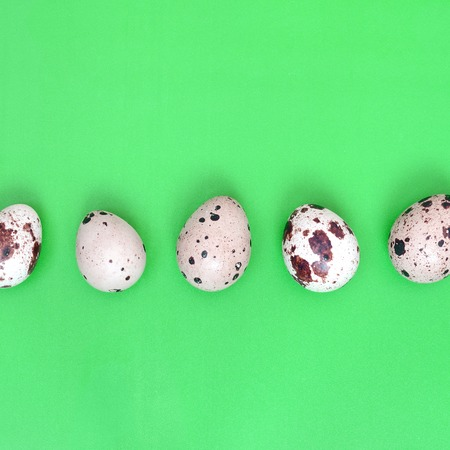 Quail eggs on a light green surface, top view, empty place for text, recipe