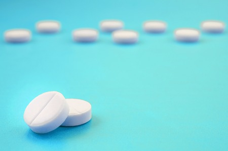 A few white tablets lie on a bright blue background surface. Background image on medical and pharmaceutical topics