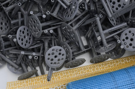 A set of construction items for the insulation of walls. Plastic dowels, a roll of mesh for the insulation of facades and a corner profile with a grid lie on the foam polystyrene surface Stock Photo