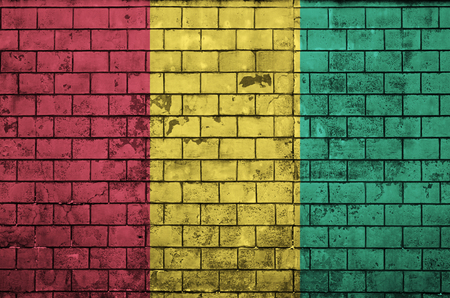 Guinea flag is painted onto an old brick wall