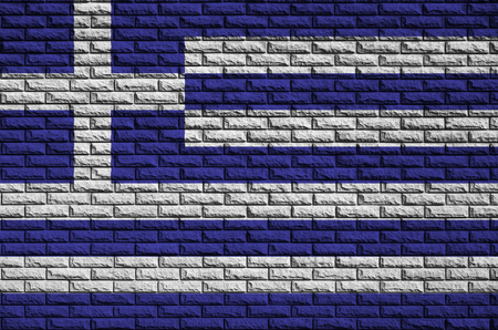 Greece flag is painted onto an old brick wall