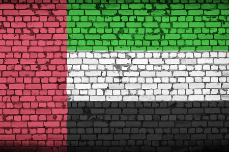 United Arab Emirates flag is painted onto an old brick wall