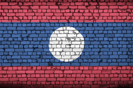 Laos flag is painted onto an old brick wall
