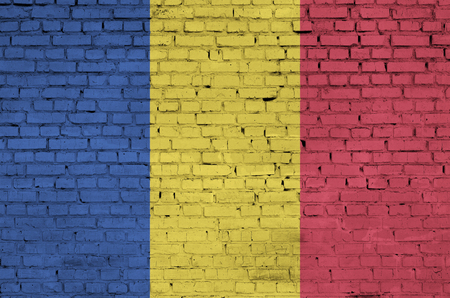 Romania flag is painted onto an old brick wall
