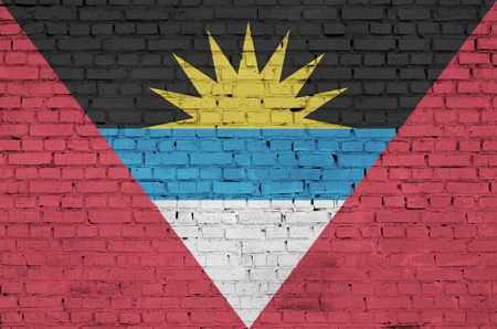 Antigua and Barbuda flag is painted onto an old brick wall