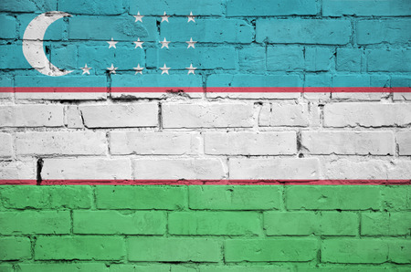 Uzbekistan flag is painted onto an old brick wall