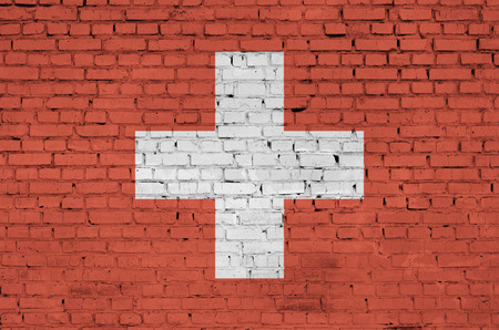 Switzerland flag is painted onto an old brick wall Banco de Imagens