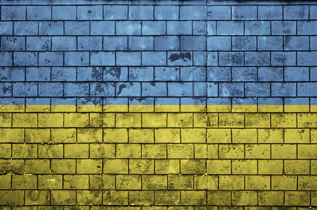 Ukraine flag is painted onto an old brick wall Banco de Imagens