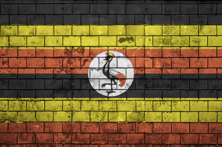 Uganda flag is painted onto an old brick wall Stock Photo