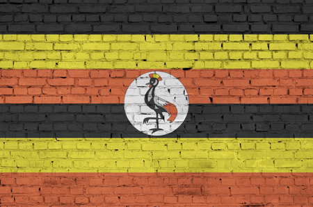 Uganda flag is painted onto an old brick wall Banco de Imagens