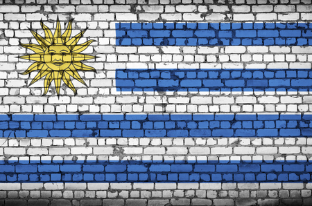 Uruguay flag is painted onto an old brick wall Banco de Imagens