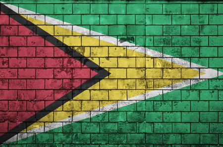 Guyana flag is painted onto an old brick wall