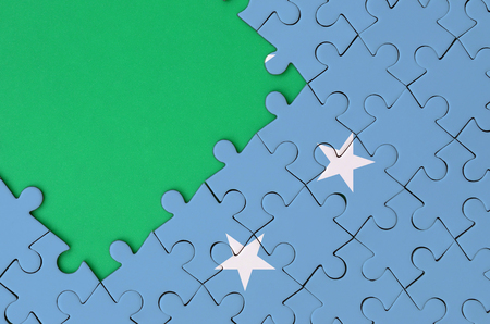 Micronesia flag  is depicted on a completed jigsaw puzzle with free green copy space on the left side.